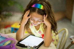 young girl leaning over a tablet