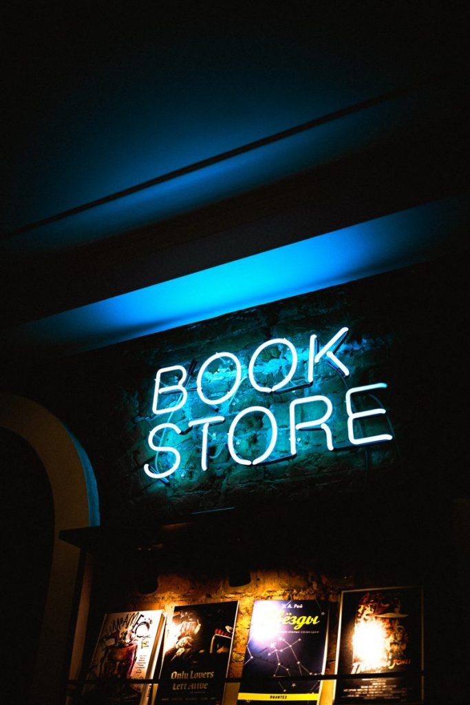 a neon sign reading'book store' above a display of books