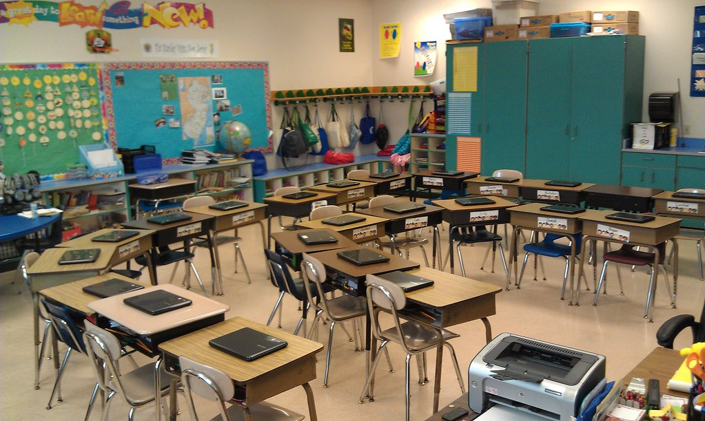 an empty classroom with a a device sitting on each desk