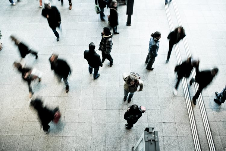 a busy public area with people blurred by the motion of their speed