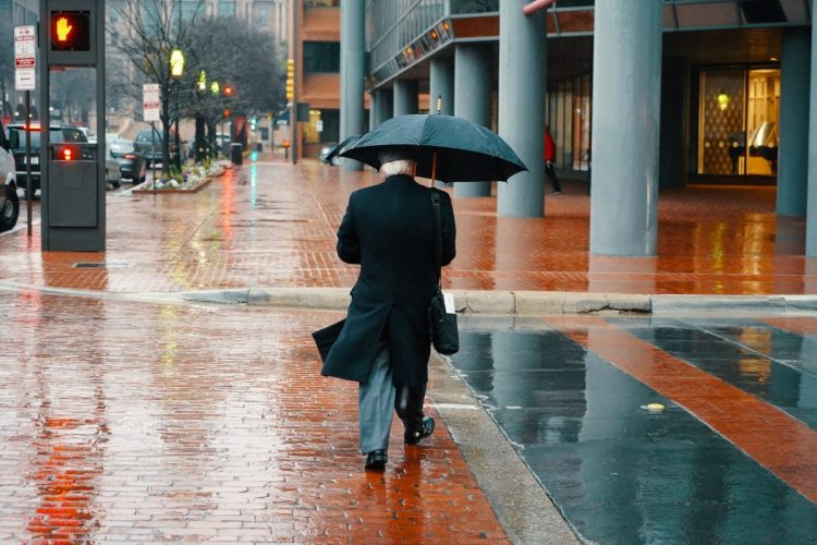 A distinguished professional approaching retirement walks to work in the rain.