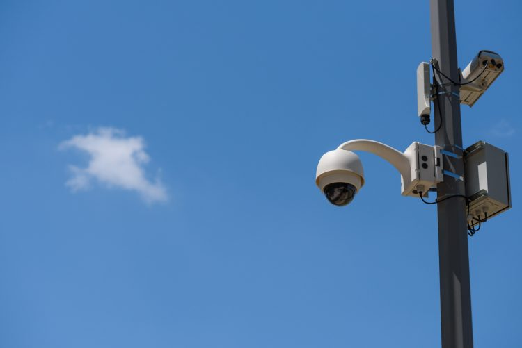 a surveillance camera mounted on a pole before a blue sky