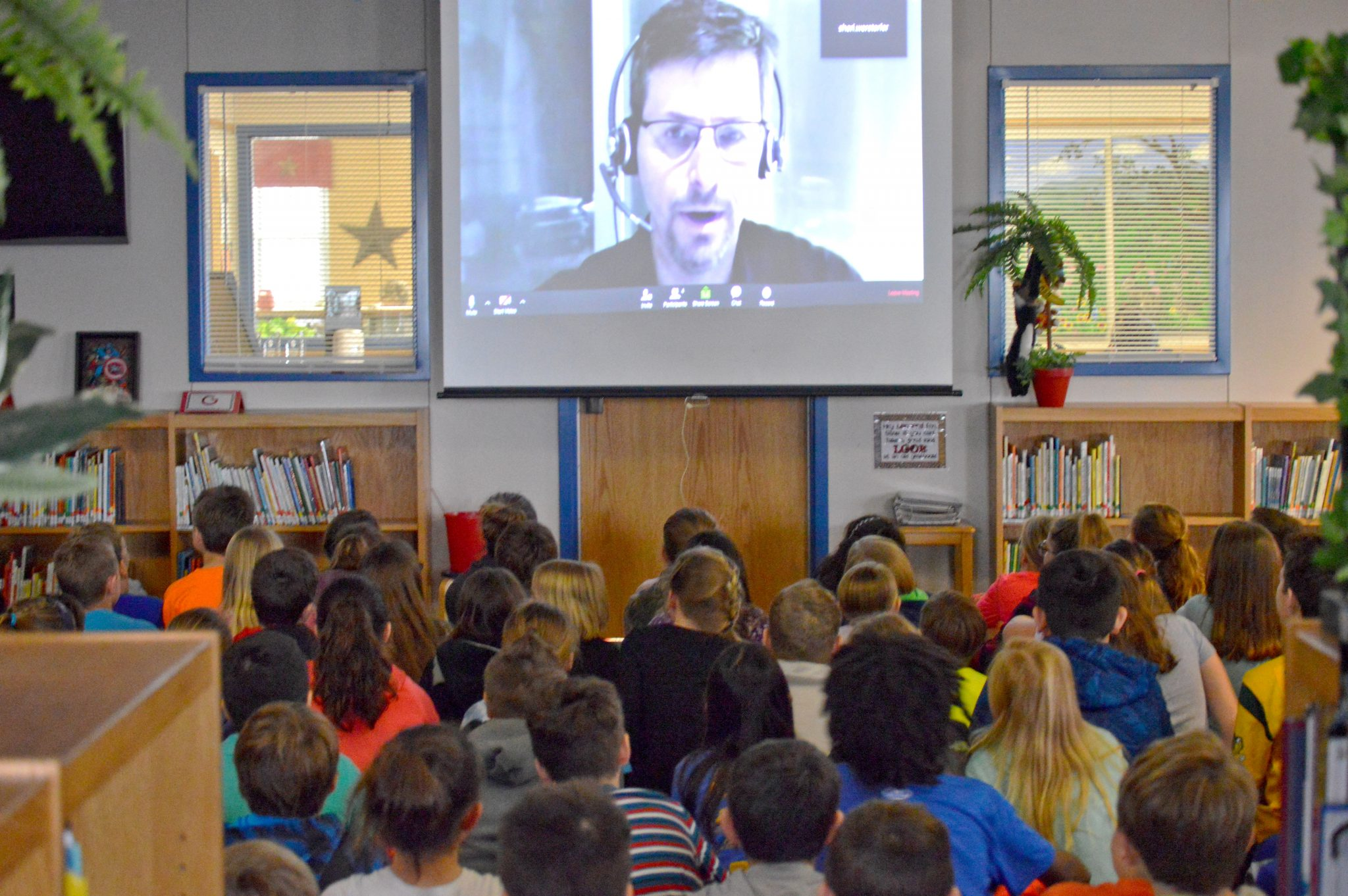 A professional addresses a class via video stream.