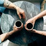 an overhead shot of two people getting coffee on a round wooden table