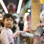 A girl holds hands with a humanoid robot
