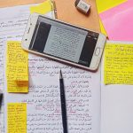 Notes and a mobile device containing arabic script sit on a desk.